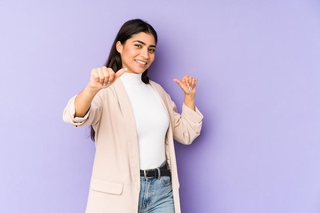 紫色の空間に孤立した若いインド人女性は、両方の親指を上げて、笑顔で自信を持っています。