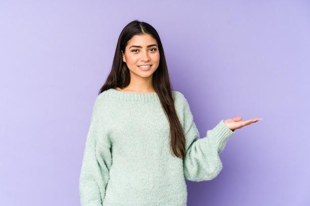 手のひらにコピースペースを示し、腰に別の手を保持している紫色のスペースに分離された若いインド人女性。
