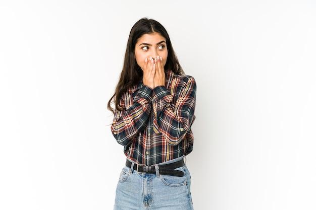手で口を覆うコピースペースを思慮深く見ている紫色のスペースに孤立した若いインド人女性。