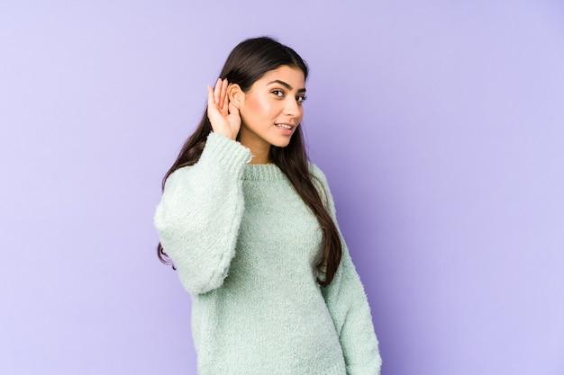 ゴシップを聴こうとしている紫色の空間に孤立した若いインド人女性。