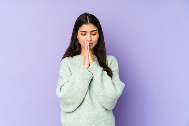 Молодая индийская женщина, изолированная на фиолетовой стене, взявшись за руки в молитве возле рта, чувствует себя уверенно.