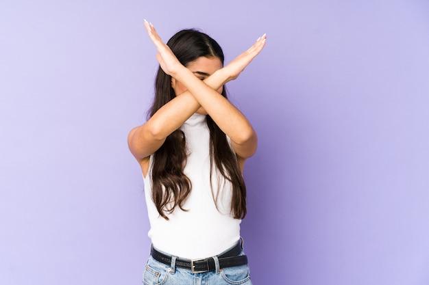 Молодая индийская женщина изолированная на фиолетовой стене держа скрещенными двумя руками, концепцией отрицания.