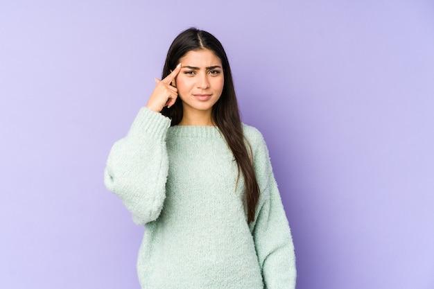 若いインド人女性は、指で寺院を指している紫色の壁に孤立し、考え、タスクに焦点を当てた。