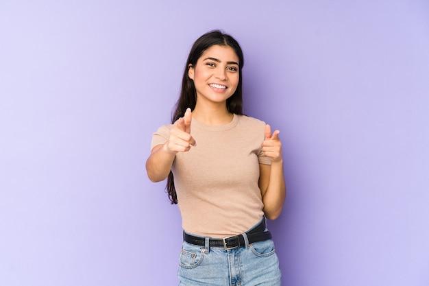 指で正面を指している紫色の壁に孤立した若いインド人女性。