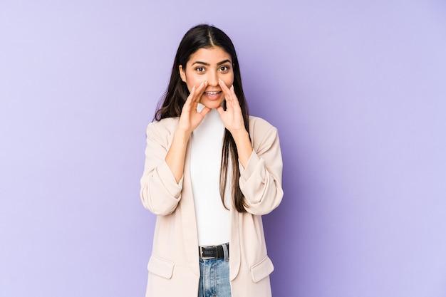 Молодая индийская женщина изолирована на фиолетовой стене, говоря сплетню, указывая на сторону, сообщающую что-то.