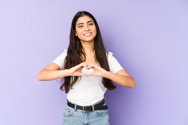 Молодая индийская женщина изолировала на фиолетовой стене усмехаясь и показывая форму сердца руками.