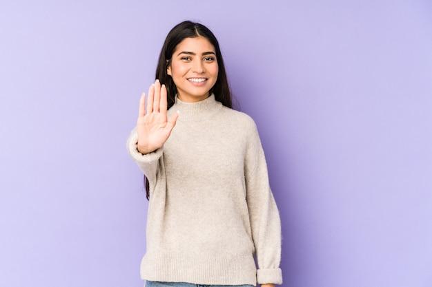 紫色の壁に孤立した若いインド人女性は、指で5番を示して陽気に笑っています。