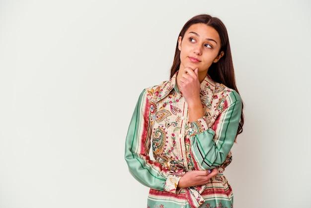 Молодая индийская женщина на белом фоне смотрит в сторону с сомнительным и скептическим выражением лица.