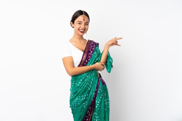 측면에 손가락을 가리키는 흰색 배경에 고립 된 젊은 인도 여자