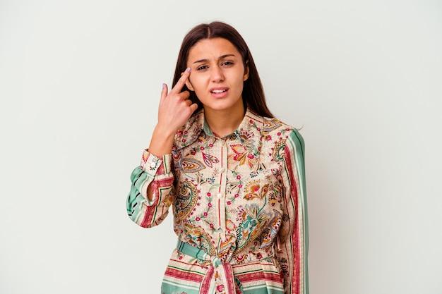 집게 손가락으로 실망 제스처를 보여주는 흰색 배경에 고립 된 젊은 인도 여자.