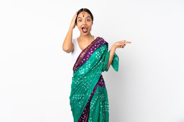 흰색에 놀랍고 측면을 가리키는 손가락에 고립 된 젊은 인도 여자