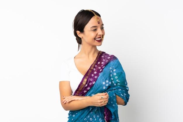 Молодая индийская женщина изолирована на белой стене, глядя в сторону и улыбается