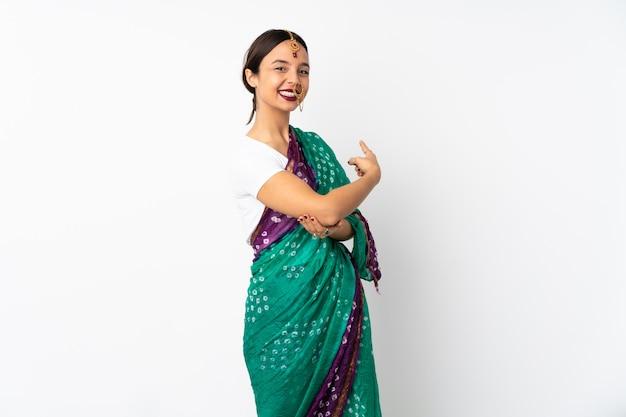 다시 가리키는 흰 벽에 고립 된 젊은 인도 여자