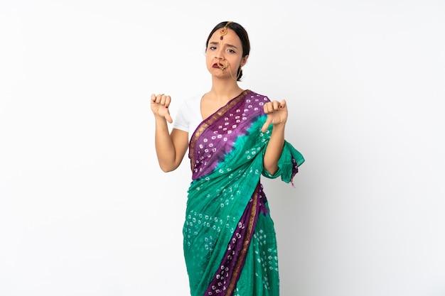 Молодая индийская женщина изолированная на белой стене показывая большой палец руки вниз с двумя руками