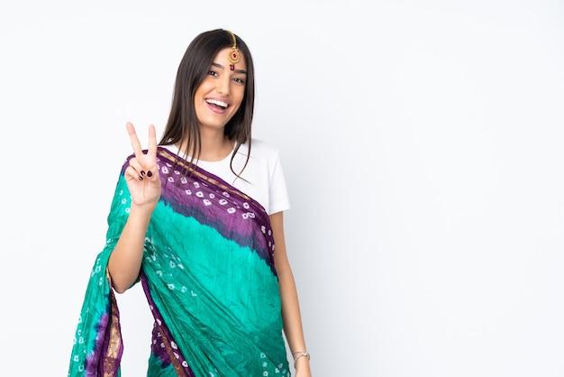 Молодая индийская женщина изолированная на белой стене усмехаясь и показывая знак победы