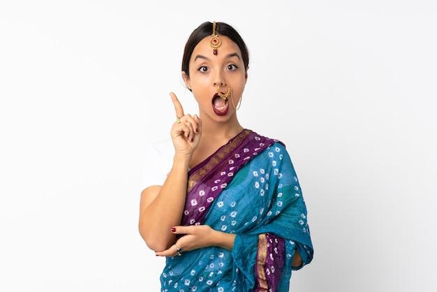 指を上に向けるアイデアを考えて白い壁に孤立した若いインドの女性