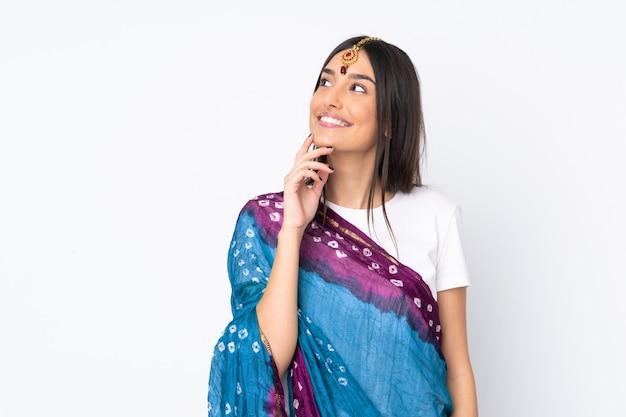 Молодая индийская женщина изолированная на белой стене думая идея пока смотрящ вверх