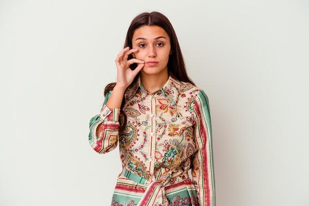 秘密を守って唇に指で白い壁に隔離された若いインド人女性。