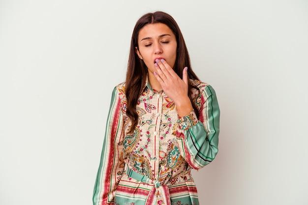 手で口を覆う疲れたジェスチャーを示すあくびをしている白い壁に孤立した若いインド人女性。