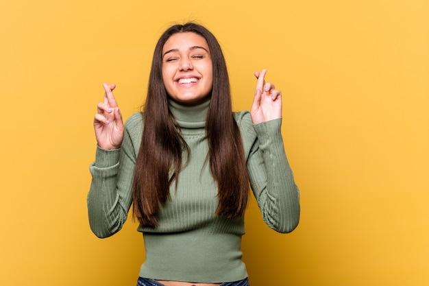 행운을 갖는 노란색 횡단 손가락에 고립 된 젊은 인도 여자