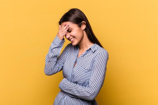 黄色い壁に孤立した若いインド人女性が指で正面を瞬き、恥ずかしい顔を覆っている