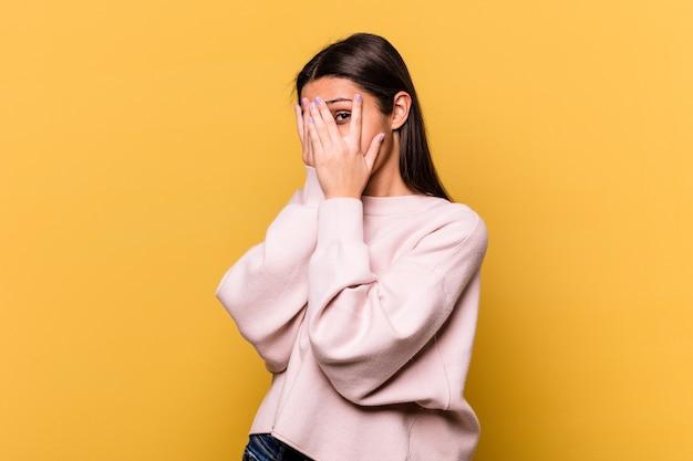 黄色い壁に隔離された若いインド人女性は、怯えて神経質な指で瞬きします。