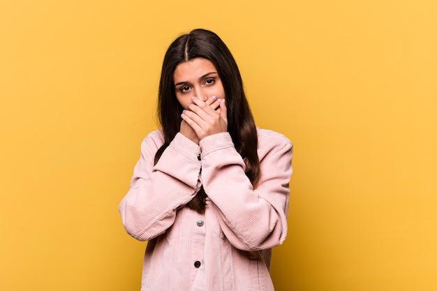걱정 찾고 손으로 입을 덮고 노란색 벽에 고립 된 젊은 인도 여자