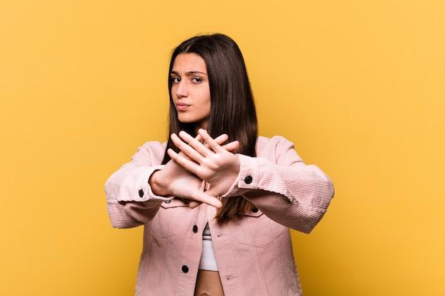 Молодая индийская женщина изолирована на желтой стене, делая жест отрицания