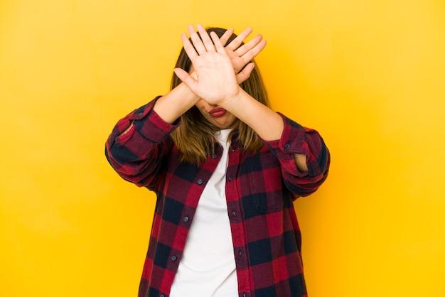 黄色の壁に孤立した若いインド人女性は、2つの腕を交差させたまま、概念を否定します。