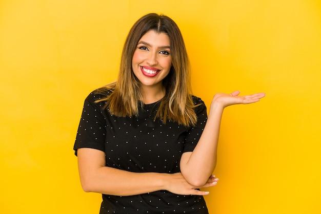 手のひらにコピースペースを示し、腰に別の手を保持している黄色の壁に分離された若いインド人女性