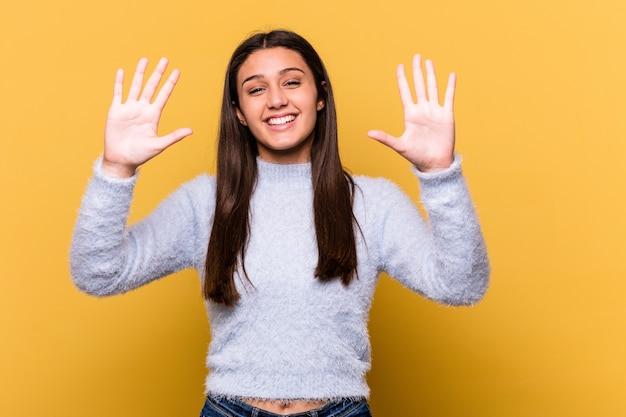 손으로 번호 10을 보여주는 노란색 벽에 고립 된 젊은 인도 여자