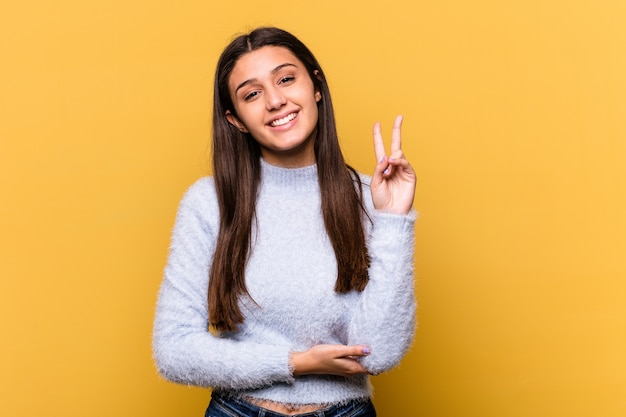 指で2番目を示す黄色の壁に隔離された若いインド人女性。