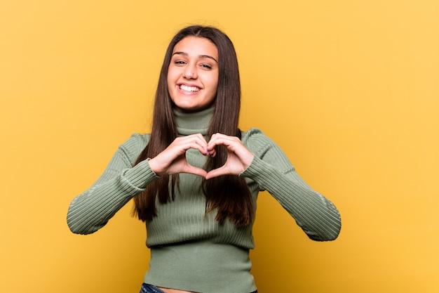 웃 고 손으로 심장 모양을 보여주는 노란색 벽에 고립 된 젊은 인도 여자