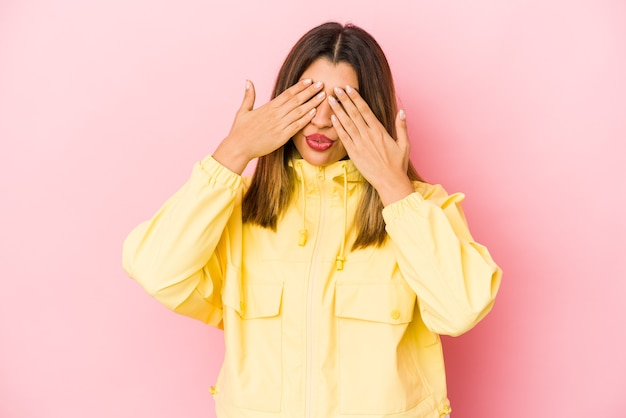 Young indian woman isolated on pink background afraid covering eyes with hands.