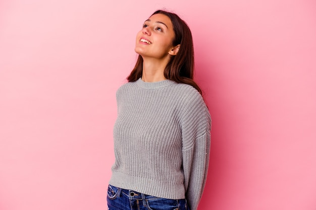 Young indian woman isolated on pink background relaxed and happy laughing, neck stretched showing teeth.