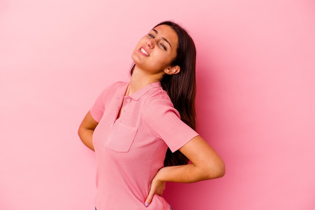 Young indian woman isolated on pink suffering a back pain.