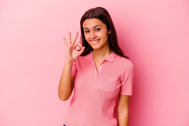 Young indian woman isolated on pink wall winks an eye and holds an okay gesture with hand.