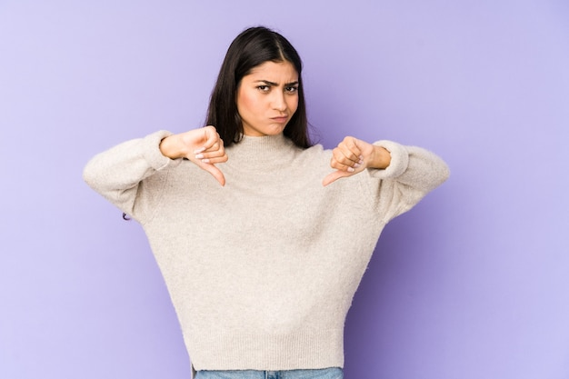 Young indian woman isolated on purple background showing thumb down, disappointment concept.