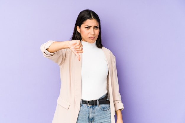 Young indian woman isolated on purple background showing thumb down and expressing dislike.