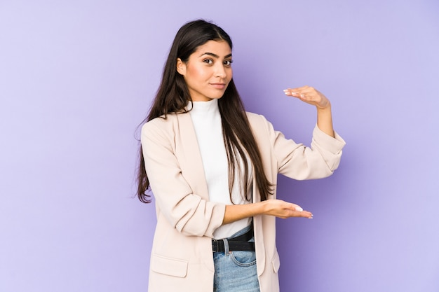 Young indian woman isolated on purple holding something with both hands, product presentation.
