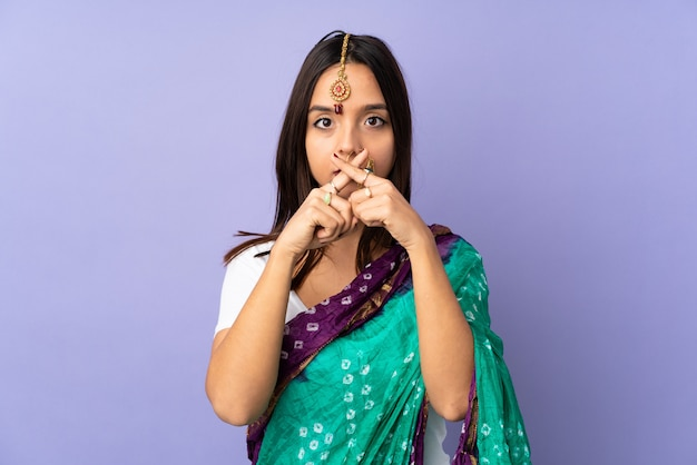 Young indian woman isolated on purple wall showing a sign of silence gesture