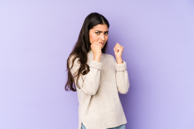 Young indian woman isolated on purple wall throwing a punch, anger, fighting due to an argument, boxing.