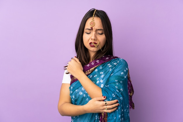 Young indian woman isolated on purple wall with pain in elbow