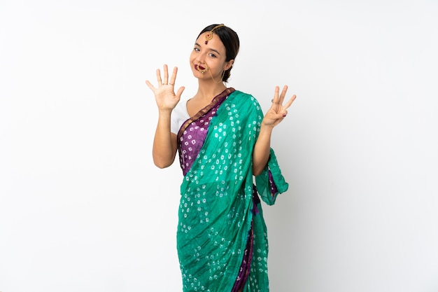 Young indian woman isolated on white wall counting eight with fingers