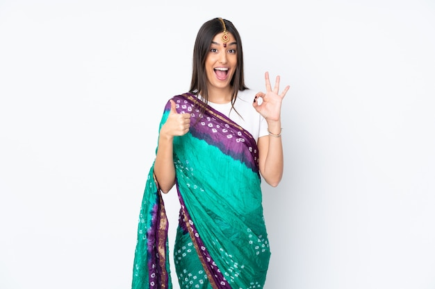 Young indian woman isolated on white wall showing ok sign and thumb up gesture
