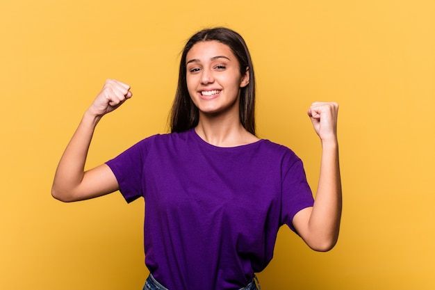 Young indian woman isolated on yellow background cheering carefree and excited. victory concept.