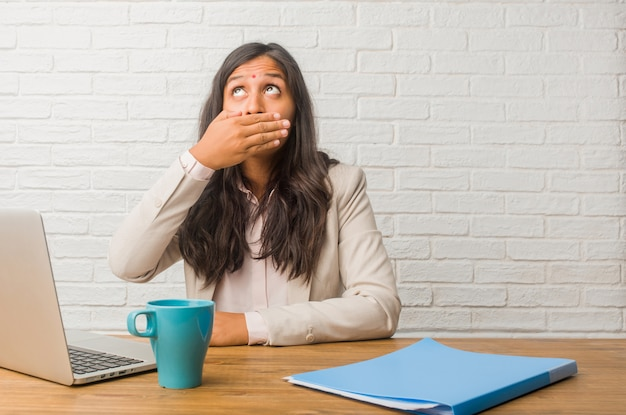 Young indian woman at the office covering mouth, symbol of silence and repression, trying not to say anything