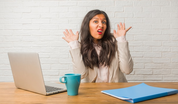 Young indian woman at the office crazy and desperate, screaming out of control, funny lunatic expressing freedom and wild