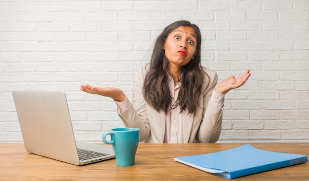 Young indian woman at the office doubting and shrugging shoulders, concept of indecision and insecurity, uncertain about something