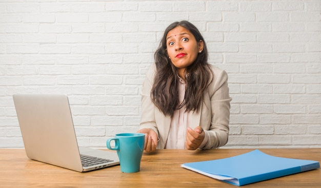 Young indian woman at the office doubting and shrugging shoulders, concept of indecision and insecurity